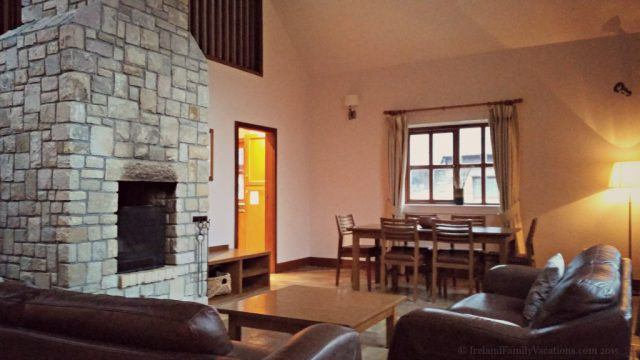 The massive stone fireplace is the central focus in the living area in the Woodland Lodges at Mount Falcon Estate in County Mayo. 3 bedrooms, 2 baths, perfect for Ireland family vacations.